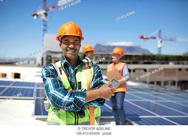 Portrait confident engineer installing solar panels on sunny rooftop