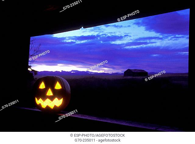 Iluminated Halloween Jack-O-Lantern in abandoned farm house