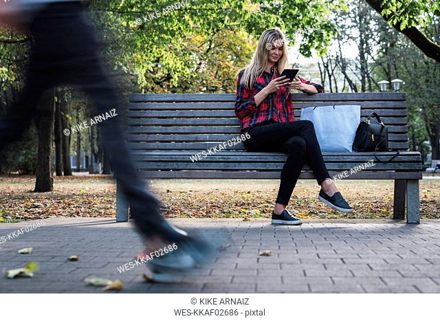 Young woman with shopping bag sitting on bench in autumn using mini tablet
