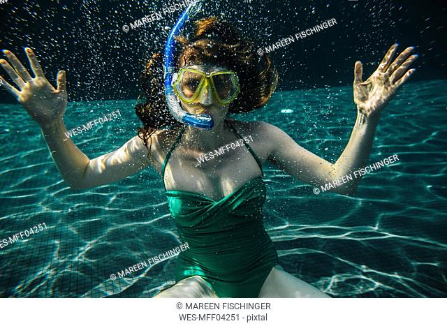 Portrait of woman with diving goggles and snorkel underwater in a swimming pool