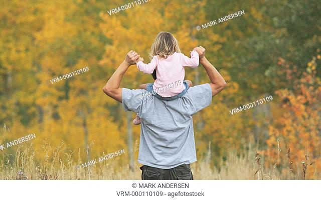 father and daughter walking through the woods