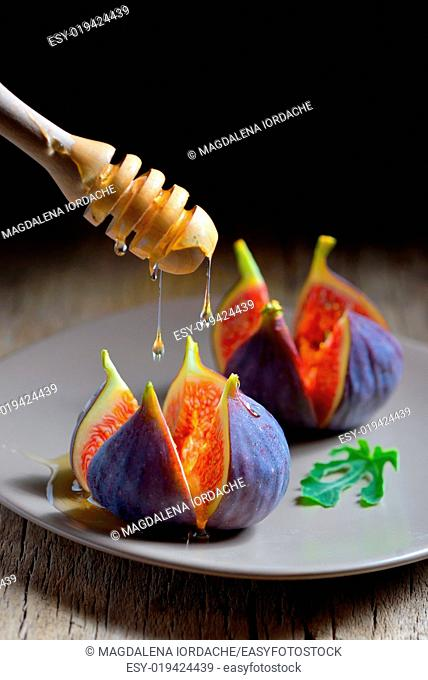 Ripe figs with honey on old wooden table
