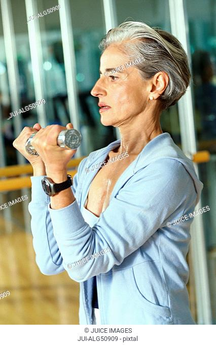 Mature woman using weights at gym