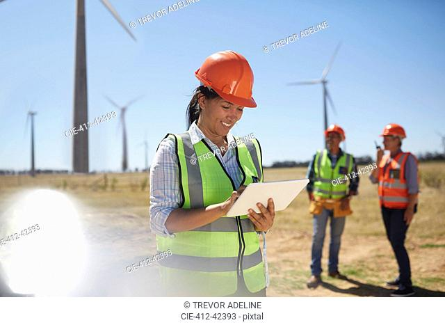 Smiling engineer using digital tablet at sunny power plant