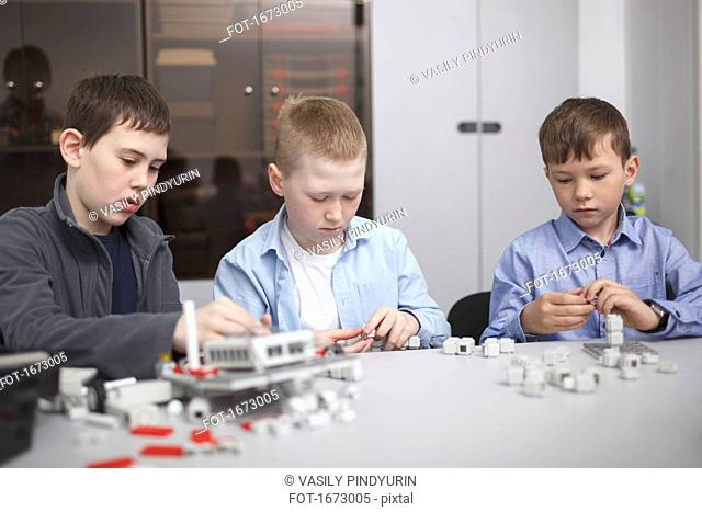 Students working on machinery at table in classroom