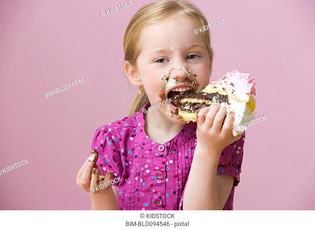 Messy girl eating birthday cake