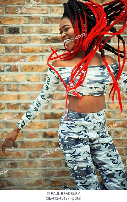 Carefree young woman in camouflage clothing dancing against brick wall
