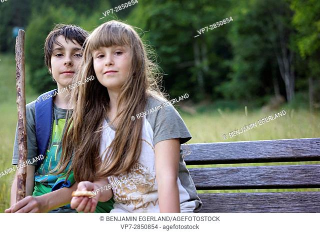 boy and girl sitting on bench during break while hiking