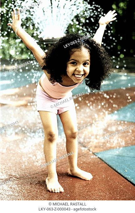 Young girl playing in fountain