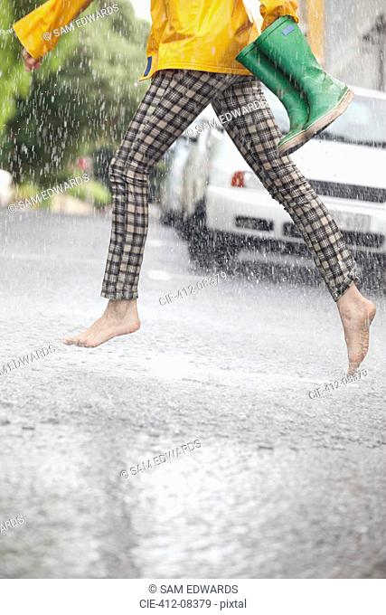 Barefoot woman running across street in rain