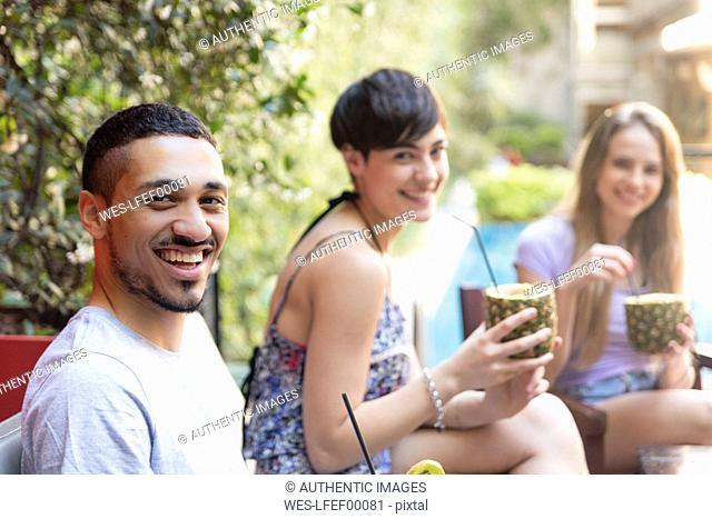 Portrait of happy friends having cocktails outside