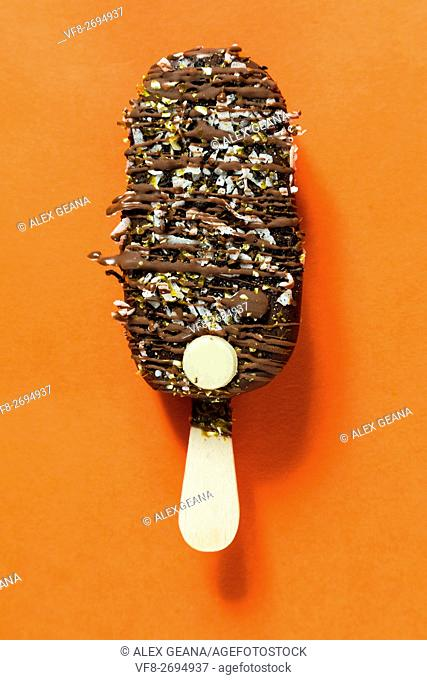 A chocolate bar isolotated on an orange background, drizled with toppings and more chocolate
