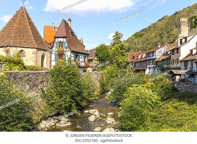 scenic corner in the center of Kaysersberg, Alsace, France, old half-timbered houses and Chapelle de l'Oberhof at the river