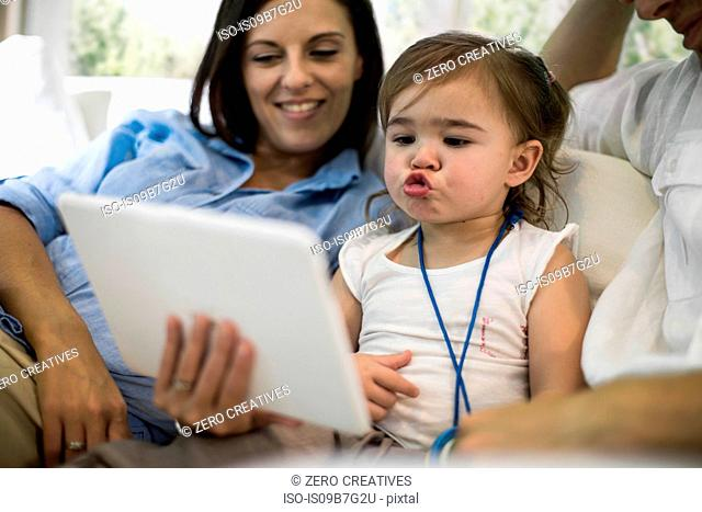 Husband and wife using digital tablet with baby girl on sofa