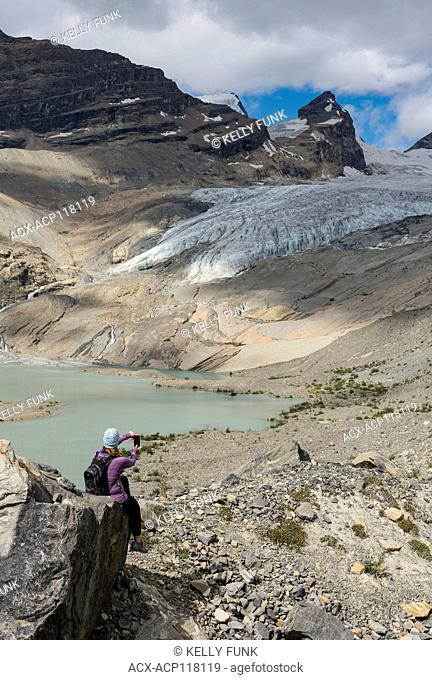 A young woman rests while at Hargreaves lake and glacier, off the Berg lake trail, Mt. Robson Provincial Park, British Columbia, Thompson Okanagan region