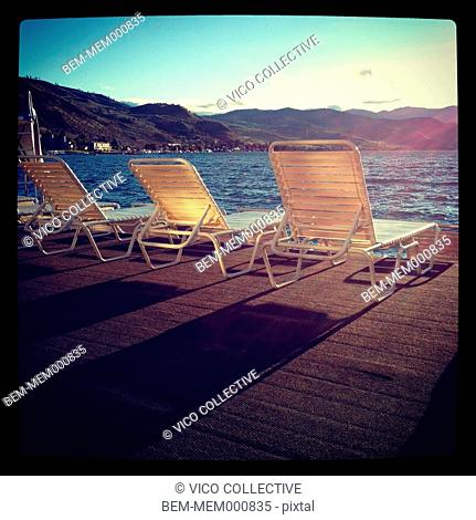Lawn chairs on deck overlooking rural lake