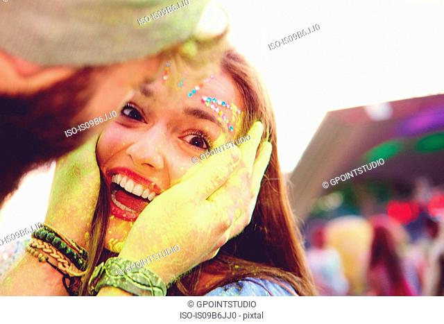 Portrait of young woman and boyfriend cupping her face with yellow chalked hand at festival