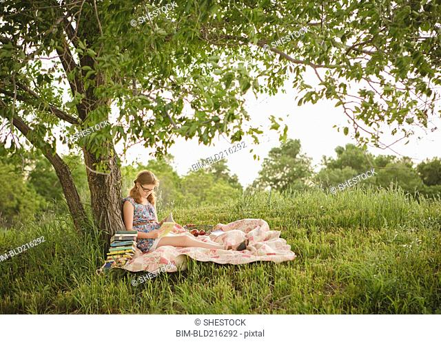 Caucasian girl reading book under tree in field