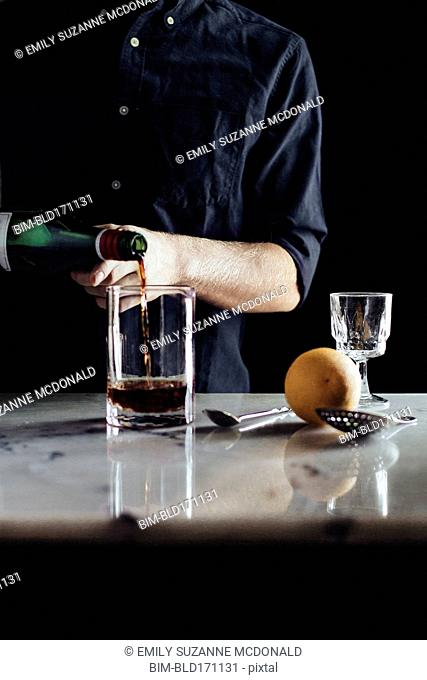 Caucasian bartender pouring cocktail in glass