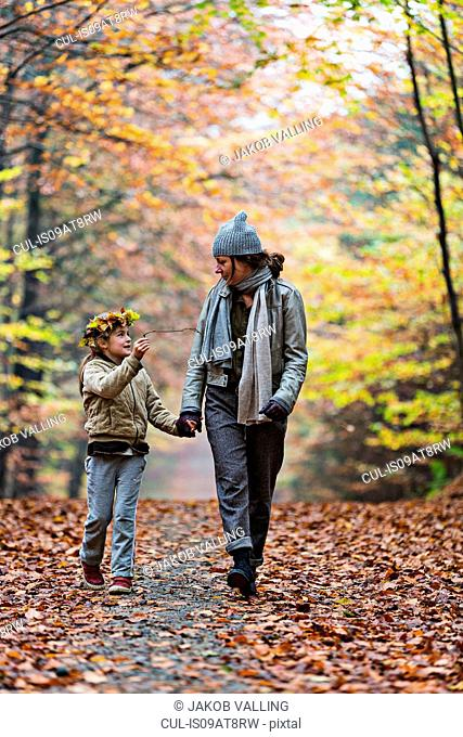 Mother and daughter walking in autumn forest
