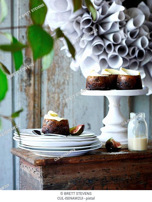 Mini christmas puddings on stack of plates on patio table