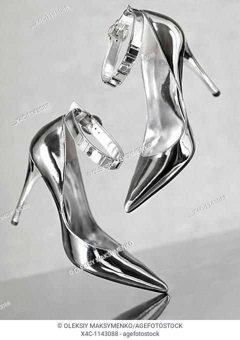 Stylish shiny silver stiletto high heel shoes falling on metal surface