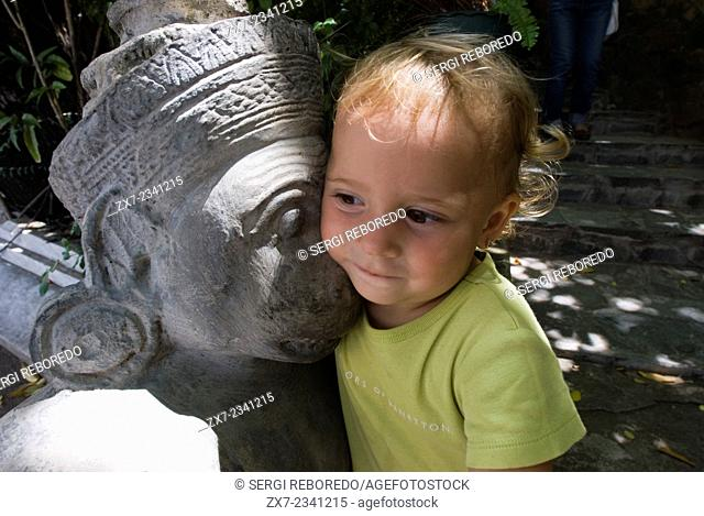 Child posing next to one of the sculptures and statues of Royal Palace. Phnom Penh. Cambodia. Asia. Travel with children's