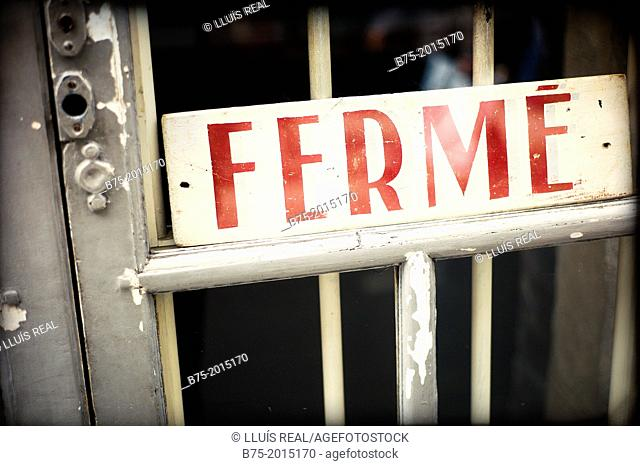 Detail of a door with a closed sign 'fermé'