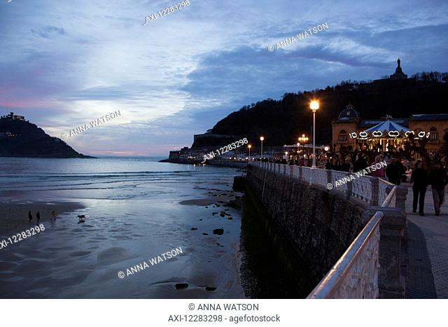 People strolling on the promenade of Passeo de La Concha at dusk, looking towards Mount Urgull with the bay of La Concha to the left; San Sebastian, Spain
