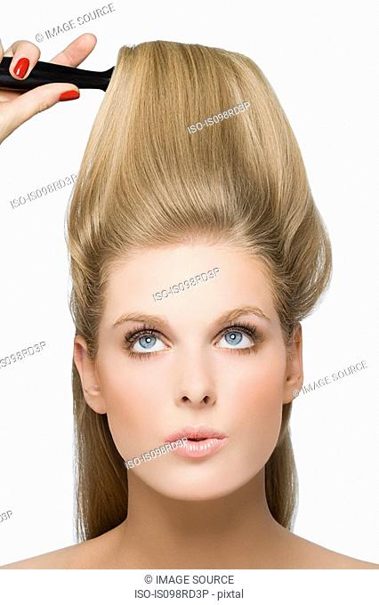 Young woman using hairbrush