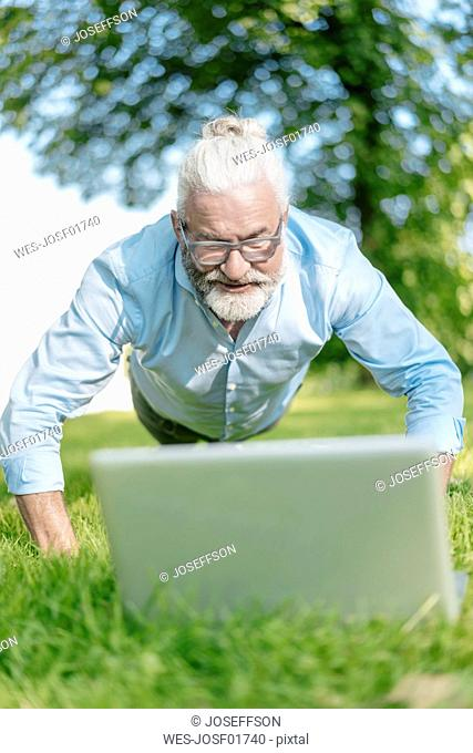 Mature man with laptop exercising in park