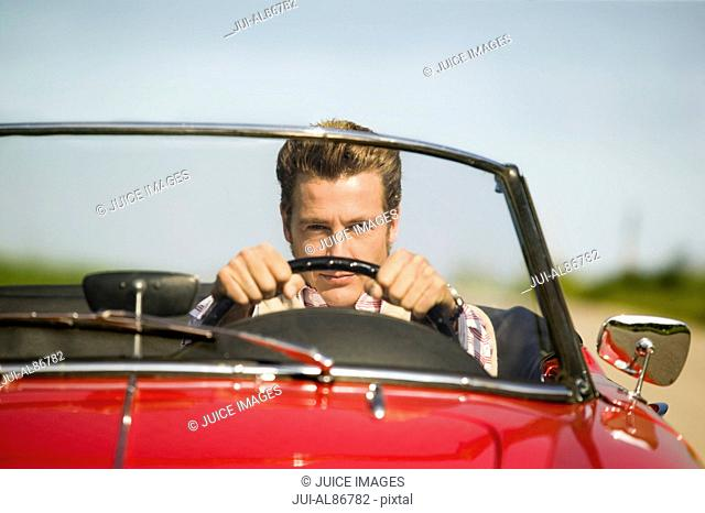 Man driving convertible in countryside