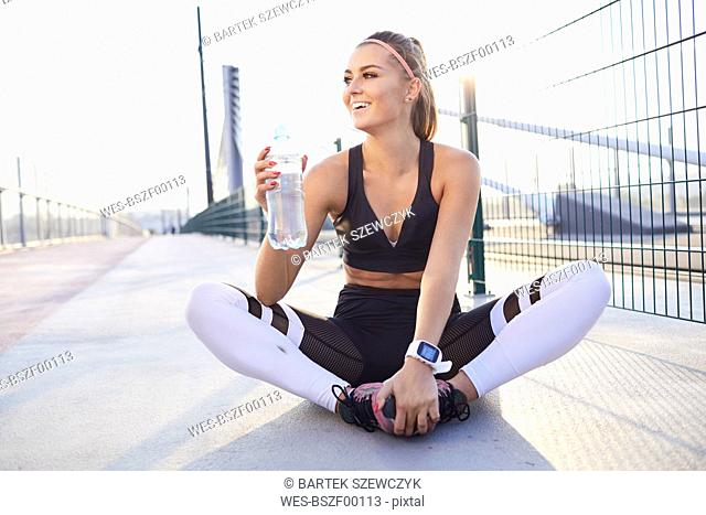 Happy female runner with bottle of water resting