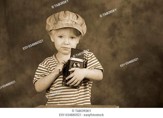 Young blond boy holding retro twin-lens reflex camera in photo studio, photographer, sepia tone