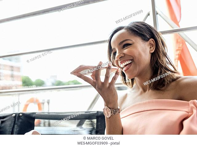 UK, London, happy beautiful woman using cell phone while traveling by boat on the River Thames