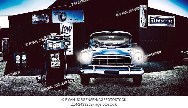 Automotive enthusiast concept with a blue 60s Australian FJ Holden parked at an old roadside garage with headlamps shining. Classic car insignia