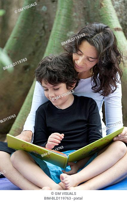 Hispanic mother and son reading outdoors