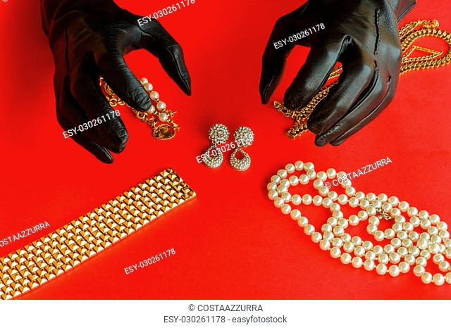 two hands wrapped in black gloves are going to steal a set of necklaces,bracelets and earrings of gold and diamonds placed on a red background