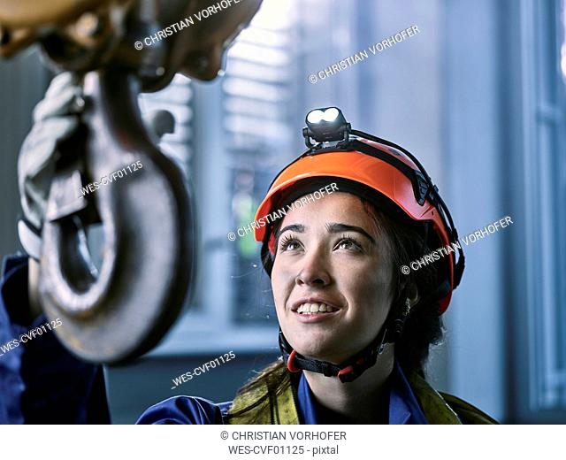 Young female industrial worker with safety helmet taking hook of indoor crane