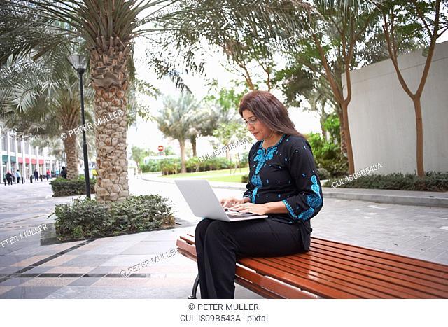 Mature businesswoman typing on laptop on park bench, Dubai, United Arab Emirates