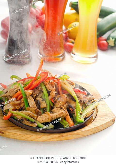 original fajita sizzling smoking hot served on iron plate, with selection of beer and fresh vegetables on background