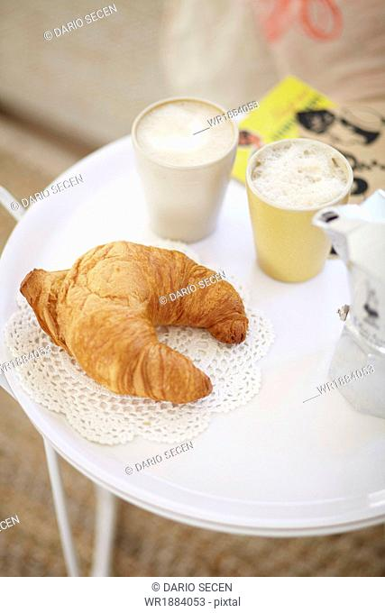 Croissant And Cup Of Coffee On Table