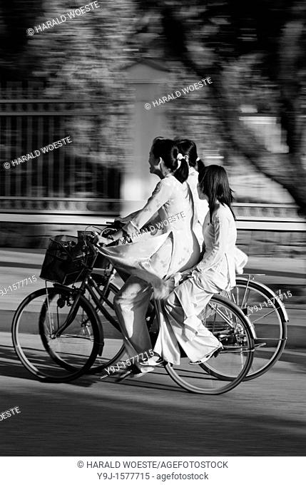 Asia, Vietnam, Hue  Girls in traditional vietnamese white dresses on bicycles returning from school