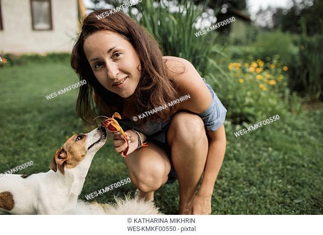 Portrait of smiling woman with Jack Russel Terrier in garden