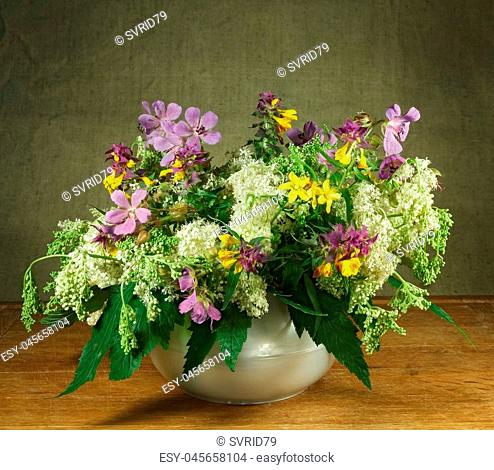 Still life. Meadow geranium, meadowsweet, hypericum perforatum, melampyrum nemorosum. Bouquet of meadow flowers in white pots standing on a wooden table
