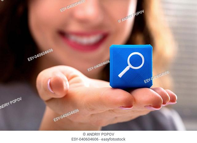 Close-up Of Woman's Hand Holding Blue Cubic Block With Magnifying Glass Icon