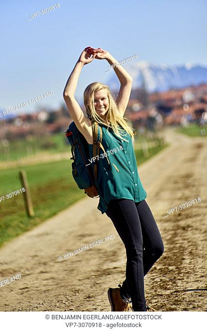 Vibrant woman hiking at country side. Waakirchen, Bavaria, Germany