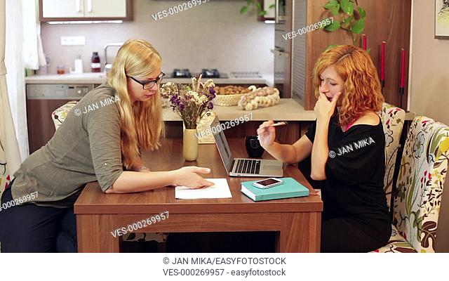 Two young women talking and writing on the paper at home