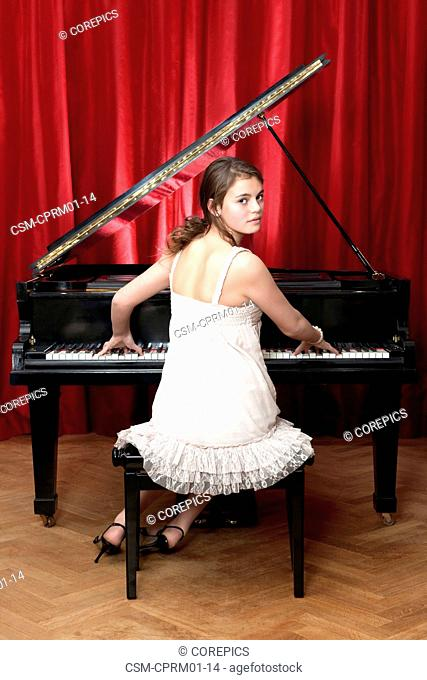 Adolescent woman playing a grand piano