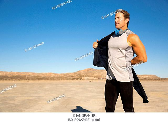 Man training, putting on tracksuit top on dry lake bed, El Mirage, California, USA